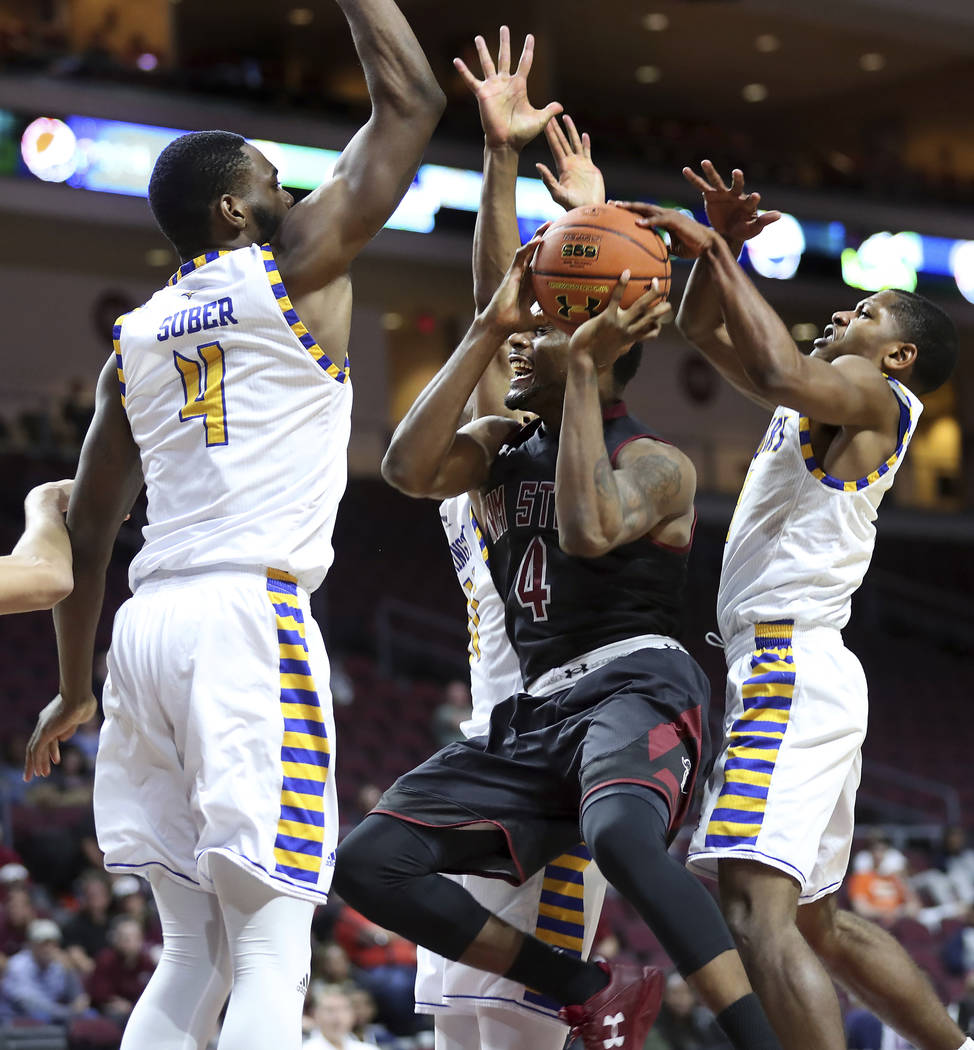 New Mexico State guard Ian Baker (4) looks for a shot in traffic while covered by Cal State Bakersfield forward James Suber (4) and guard Dedrick Basile (5) during the second half of an NCAA colle ...