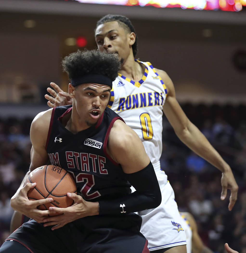 New Mexico State forward Eli Chuha (22) secures the ball with Cal State Bakersfield forward Matt Smith (0) defending during the second half of their NCAA college basketball game in the final of th ...