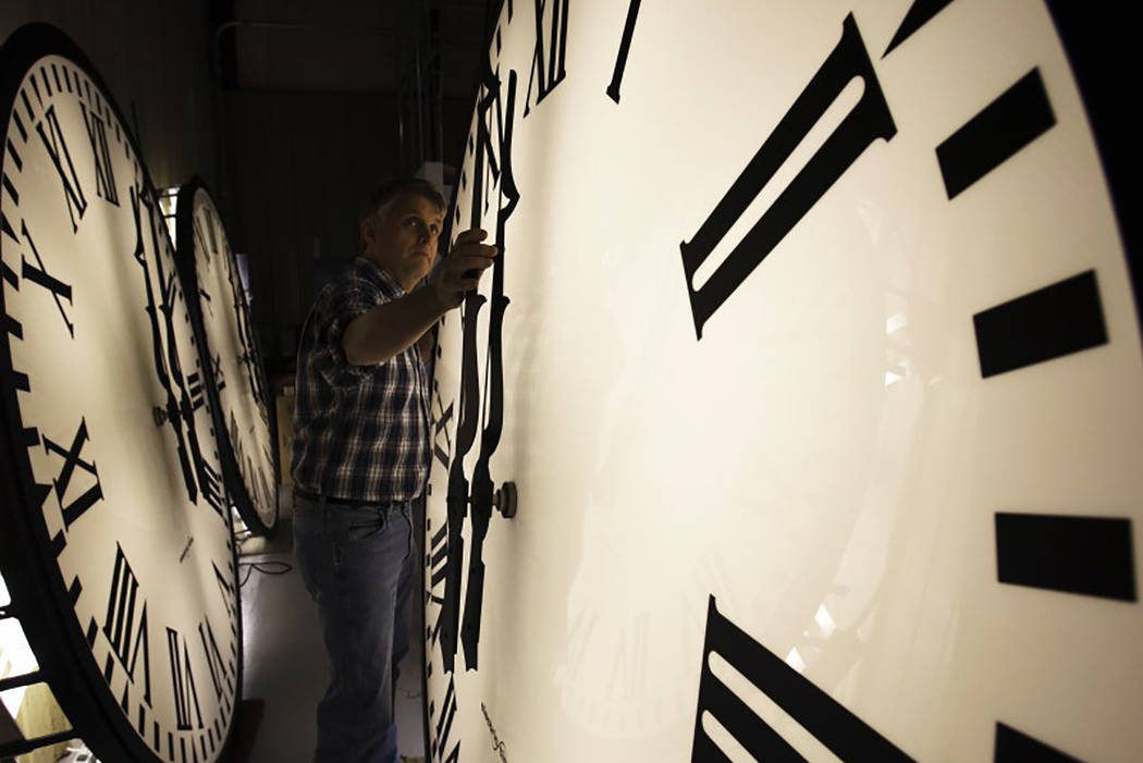 Scott Gow adjusts a tower clock on test at the Electric Time Company in Medfield, Massachusetts on March 6, 2009. (REUTERS/Brian Snyder)