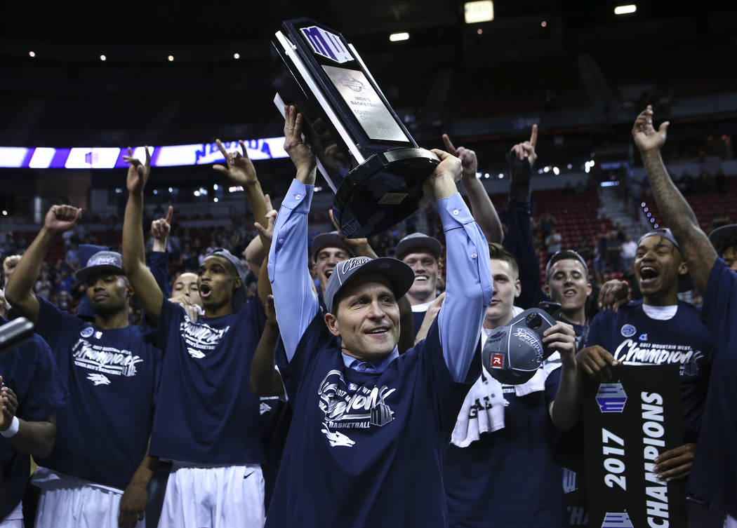 UNR head coach Eric Musselman lifts up the trophy while celebrating with his team after defeating Colorado State 79-71 in the Mountain West Conference basketball championship game at the Thomas &a ...