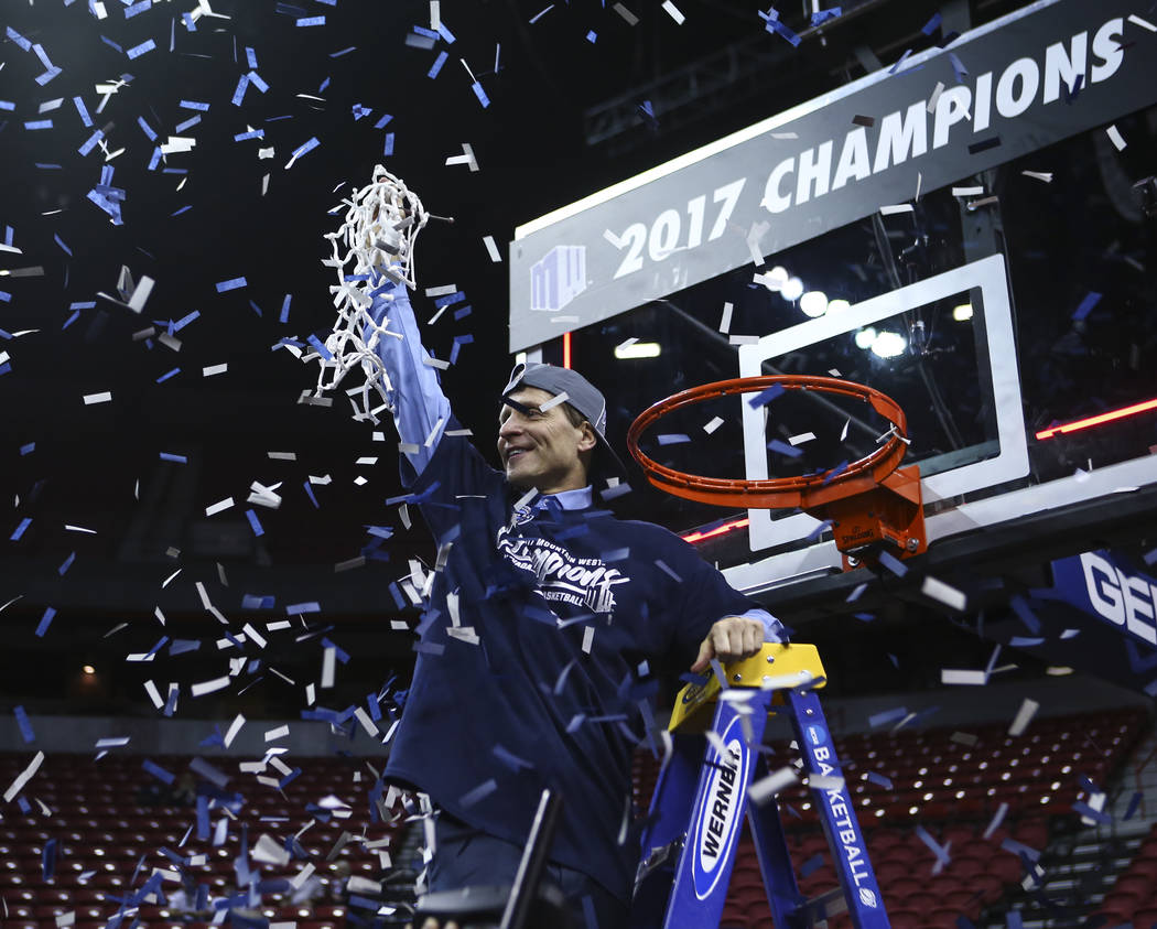 UNR head coach Eric Musselman raises the net after defeating Colorado State 79-71 in the Mountain West Conference basketball championship game at the Thomas & Mack Center in Las Vegas on Satur ...
