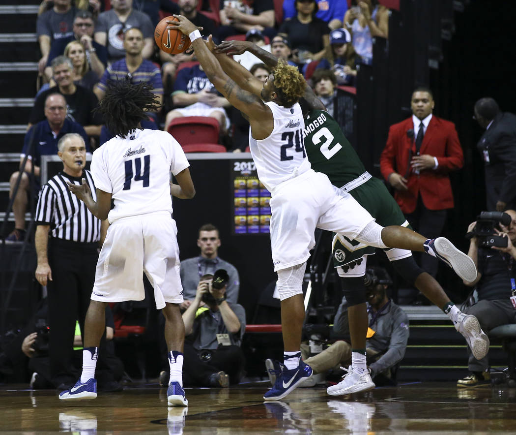 UNR guard Jordan Caroline (24) gets a rebound over Colorado State forward Emmanuel Omogbo (2) during the Mountain West Conference basketball championship game at the Thomas & Mack Center in La ...