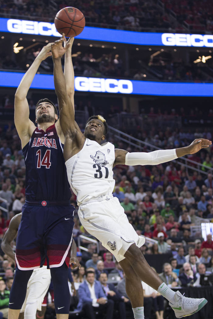 Arizona Wildcats center Dusan Ristic (14) and Oregon Ducks guard Dylan Ennis (31) fight for the ball in an NCAA college basketball game for the Pac-12 tournament championship at T-Mobile Arena Sat ...