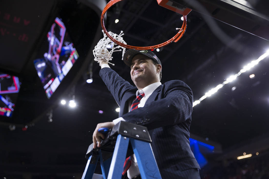 Arizona Wildcats head coach Sean Miller cuts off a net after his team's victory against Oregon Ducks in an NCAA college basketball game for the Pac-12 tournament championship at T-Mobile Arena Sat ...