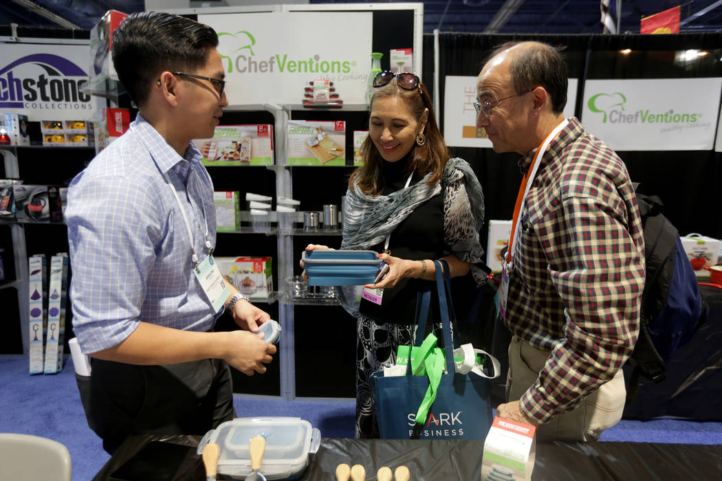 Arrione Garcia, from left, employee of Next Products, shows stackable tupperware to Wanya Ogata and her husband Duane Ogata at the ASD trade show on Sunday, March 19, 2017, at the Las Vegas Conven ...