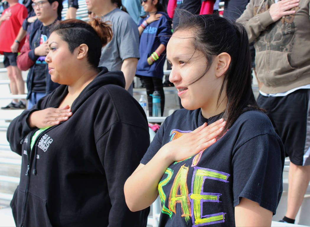 Silvia Kalb, left and Carroll M. Johnston Middle School student, Sarina Cervacio, 13, stand for the Pledge of Allegiance at Palo Verde High School during the March Forward for Suicide Awareness 5K ...
