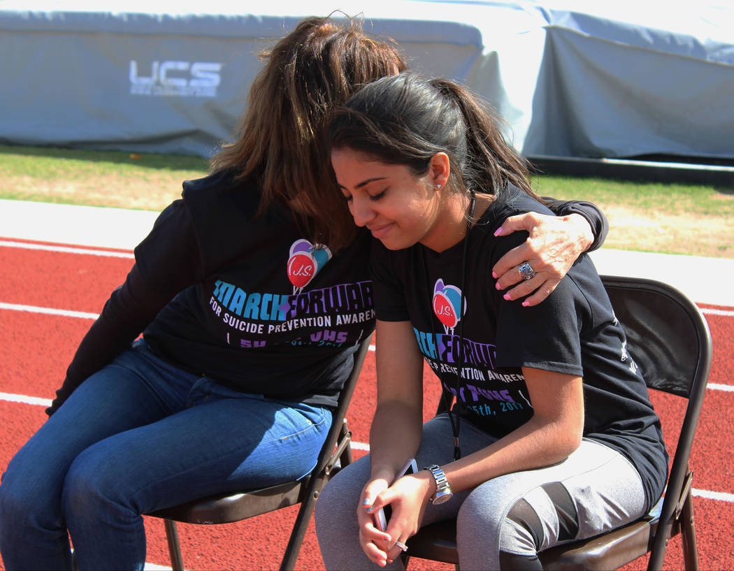 Simran Sodhi, 17, right, is comforted by event organizer, Michele Brown, after speaking about her little brother before the March Forward for Suicide Awareness 5K Walk, Saturday, March 25, 2017. ( ...