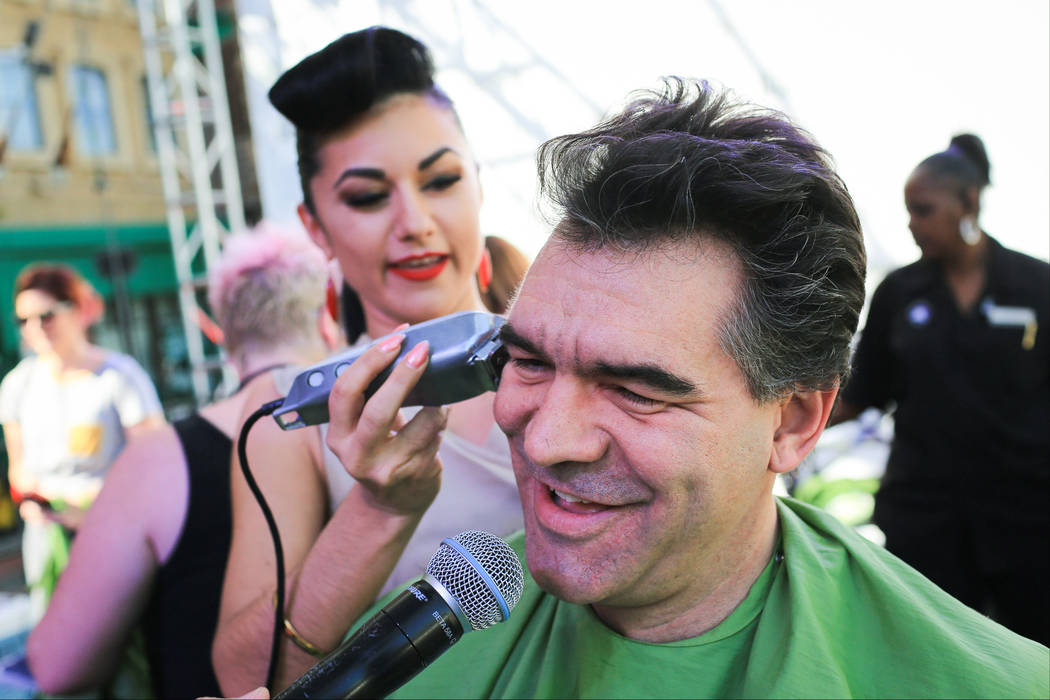 Las Vegas Review-Journal columnist John Katsilometes shows off his new hair cut given by Melody Sweets, who plays the Green Fairy in the Absinthe show at Caesars Palace, during a St. Baldrick's Fo ...