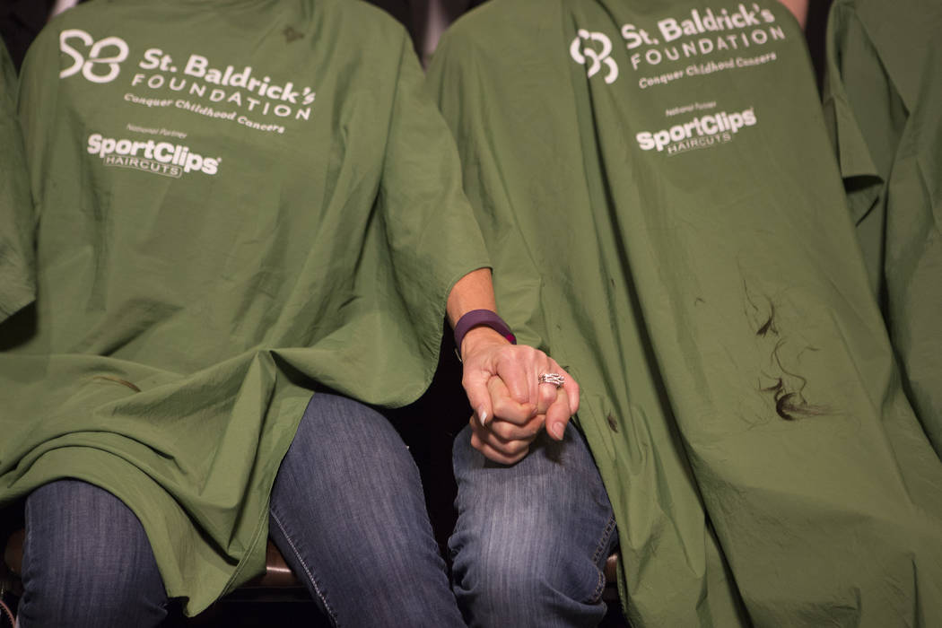 "Kathy Haynie, left, holds Shaun Haynie's, her step-son, hand while they get their heads shaved part of ""Shave for the Cure"" a St. Baldrick's event held at McMullan's Irish Pub on ..."