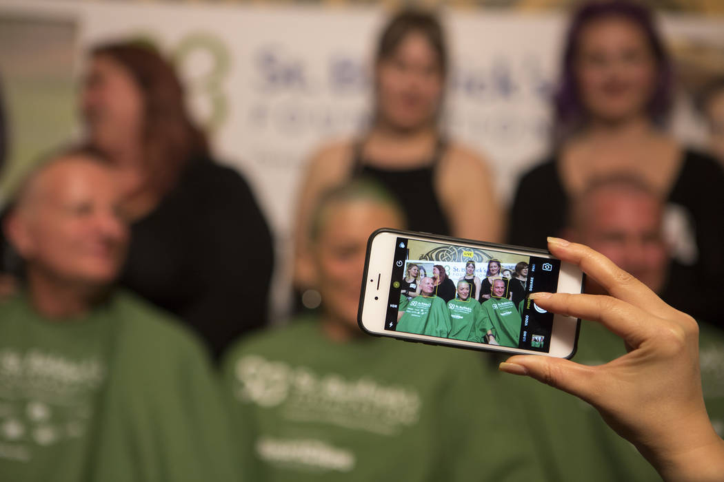 "An attendee take a photo of people who shaved their heads in part of ""Shave for the Cure"" a St. Baldrick's event held at McMullan's Irish Pub on Saturday, March 4, 2017, in Las V ..."