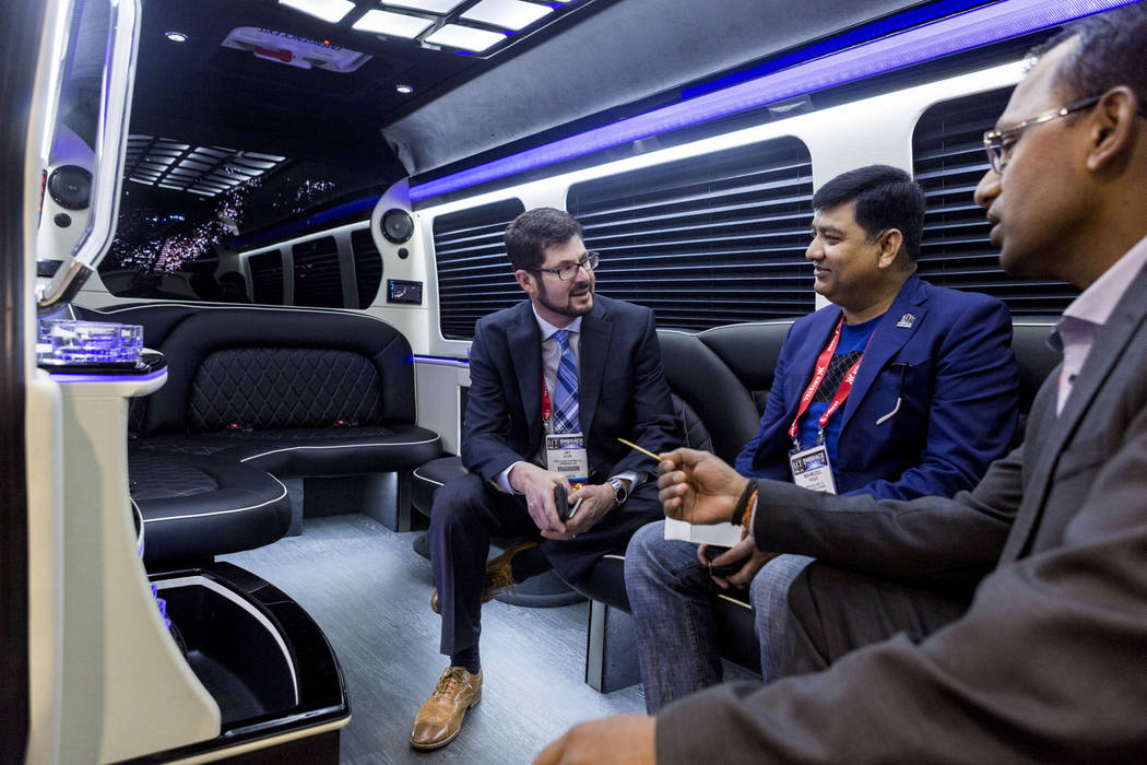 Jay M. Glick, president of First Class Customs INC., left, speaks with Jay Selva with Exotic Limousine Vancouver, center, and Mahmudul Hoque with Princess Limo LTD. during a tour of a luxury bus a ...