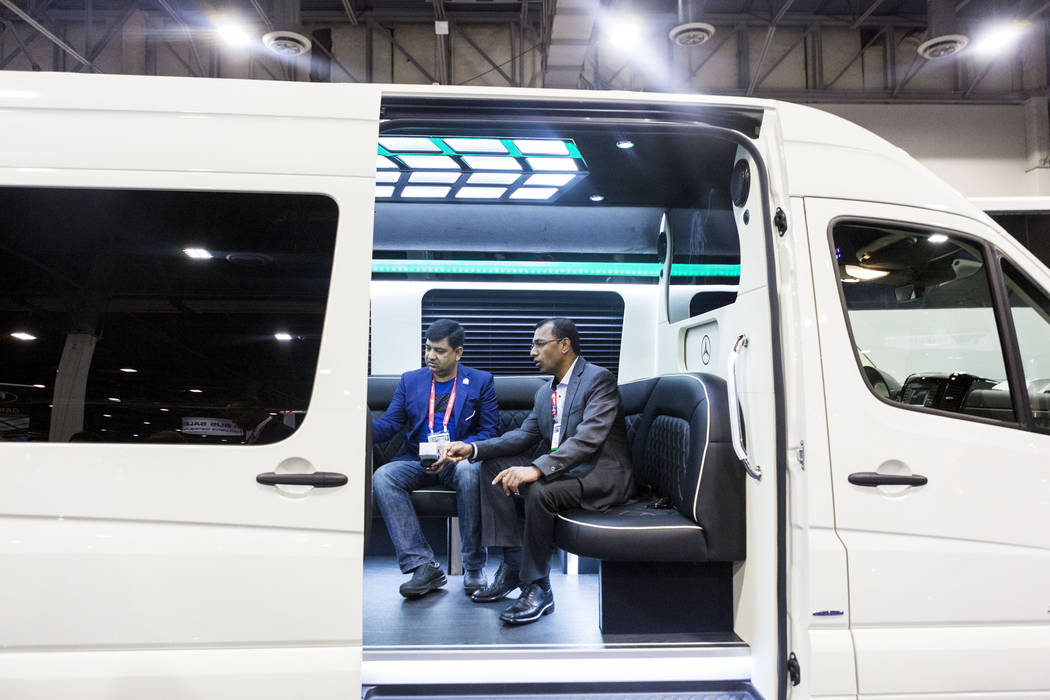 Jay Selva with Exotic Limousine Vancouver, center, and Mahmudul Hoque with Princess Limo LTD., get a tour of a luxury bus during a tour of a luxury bus at the International LCT Show at The Venetia ...