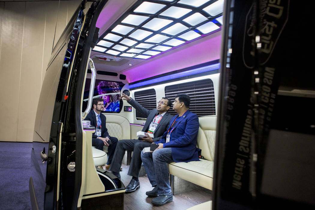 Jay M. Glick, president of First Class Customs INC., left, speaks with Jay Selva with Exotic Limousine Vancouver, center, and Mahmudul Hoque with Princess Limo LTD., during a tour of a luxury bus  ...