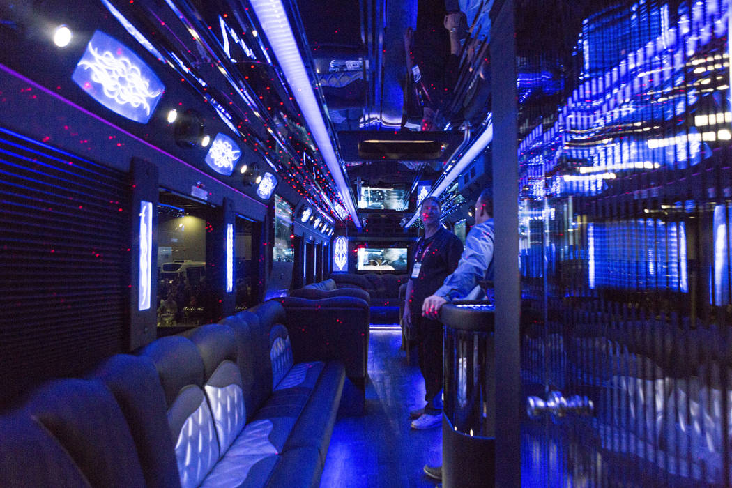Steve Thomas of CT Coachworks, left,  speaks to an attendee inside of his company's party bus during the International LCT Show at The Venetian and the Palazzo in Las Vegas, Tuesday, March 14, 201 ...