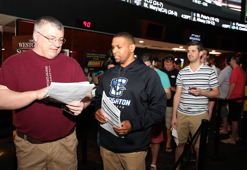 Tom Kellehur, left, and Greg Mercer discuss about their bet as they wait in line to bet on the NCAA basketball tournament at Westgate sports book on Thursday, March 16, 2017, in Las Vegas. (Bizuay ...