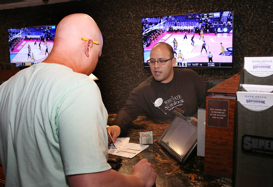 Ryan Ward, left, of Phoenix, Ariz., places his bet on the NCAA basketball tournament at Westgate sports book on Thursday, March 16, 2017, in Las Vegas. (Bizuayehu Tesfaye/Las Vegas Review-Journal) ...
