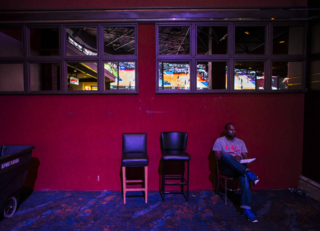 Donald Hodges of Rancho Cucamonga, Calif. watches games, reflected above, during the first day of the NCAA basketball tournament at the Westgate sports book in Las Vegas on Thursday, March 16, 201 ...