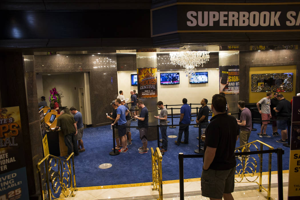 People line up to place bets at a satellite betting location in the Westgate hotel-casino during the first day of the NCAA basketball tournament in Las Vegas on Thursday, March 16, 2017. (Chase St ...