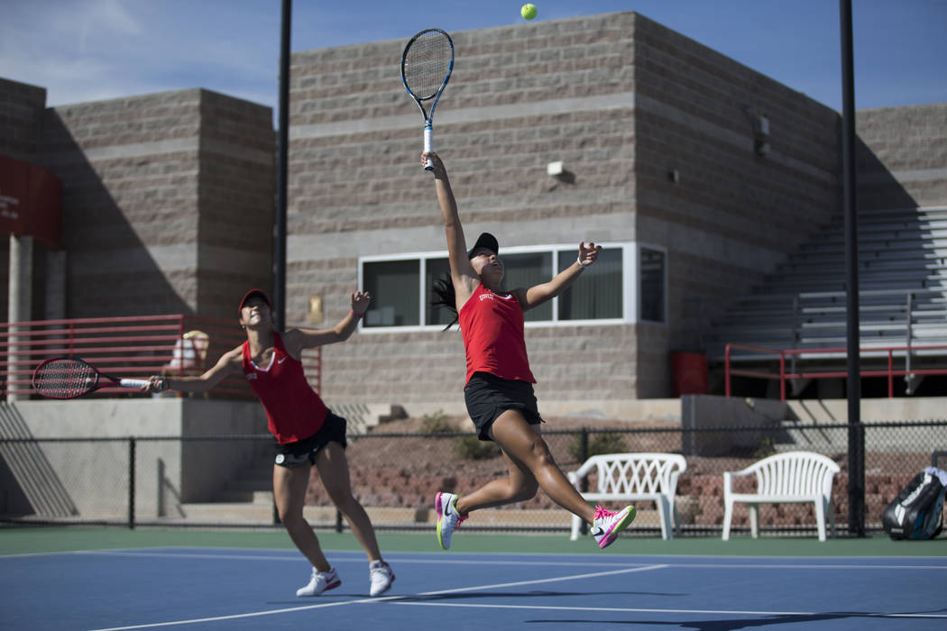 UNLV tennis player Aiwen Zhu, left, looks on as her teammate En-Pei Huang leaps to hit the ball in their doubles match against Washington State at UNLV on Wednesday, March 15, 2017, in Las Vegas.  ...