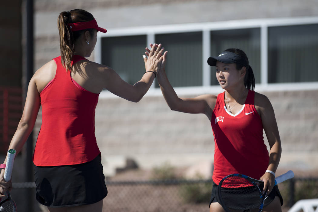 UNLV tennis player Aiwen Zhu, left, and her teammate En-Pei Huang high five after a play in their doubles match against Washington State at UNLV on Wednesday, March 15, 2017, in Las Vegas. (Erik V ...