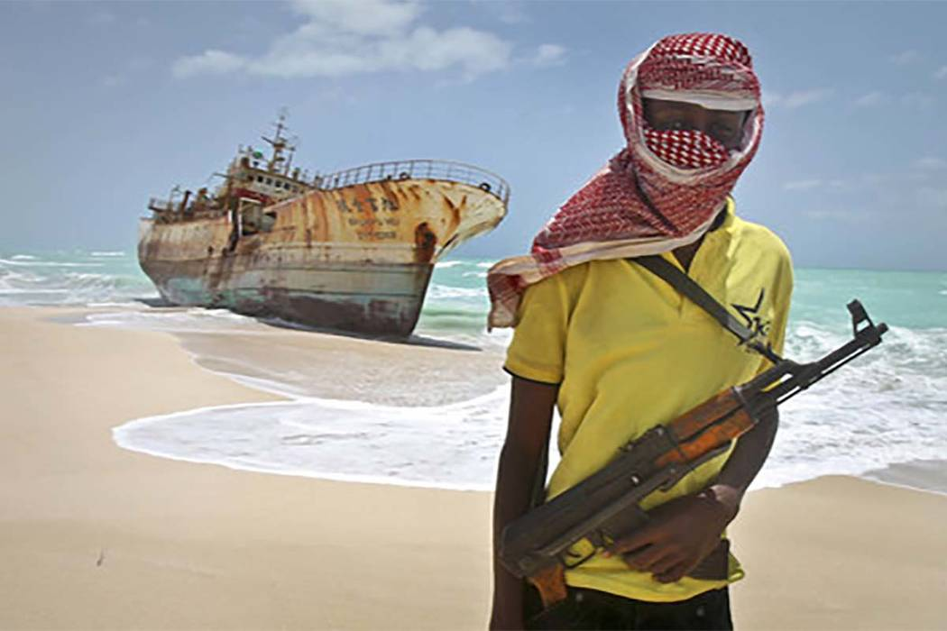 In this Sunday, Sept. 23, 2012 file photo, masked and armed Somali pirate Hassan stands near a Taiwanese fishing vessel washed ashore after the pirates were paid a ransom and the crew was released ...
