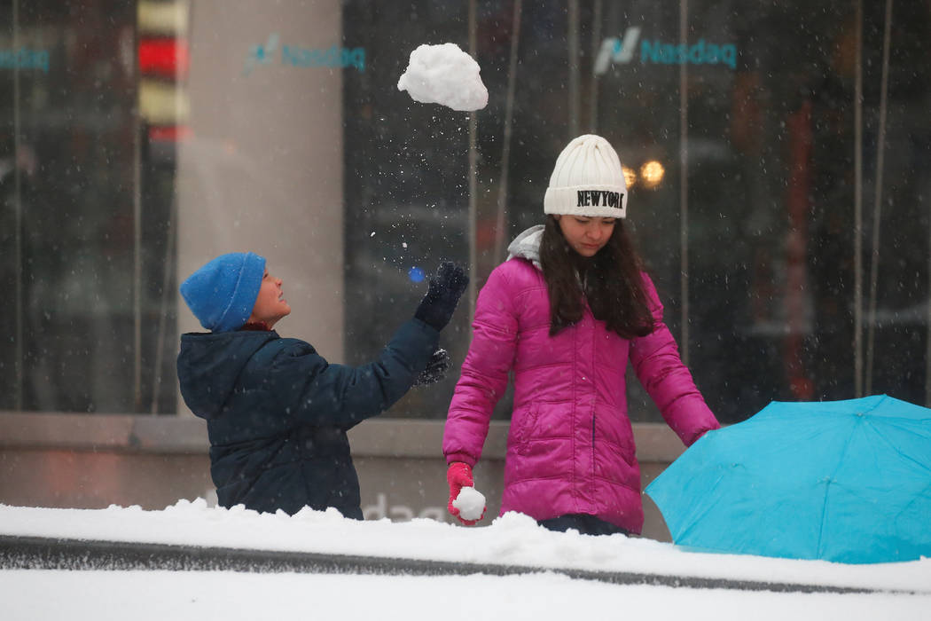 Children play in the snow in Times Square during a snowstorm in the Manhattan borough of New York, March 14, 2017. (Carlo Allegri/Reuters)