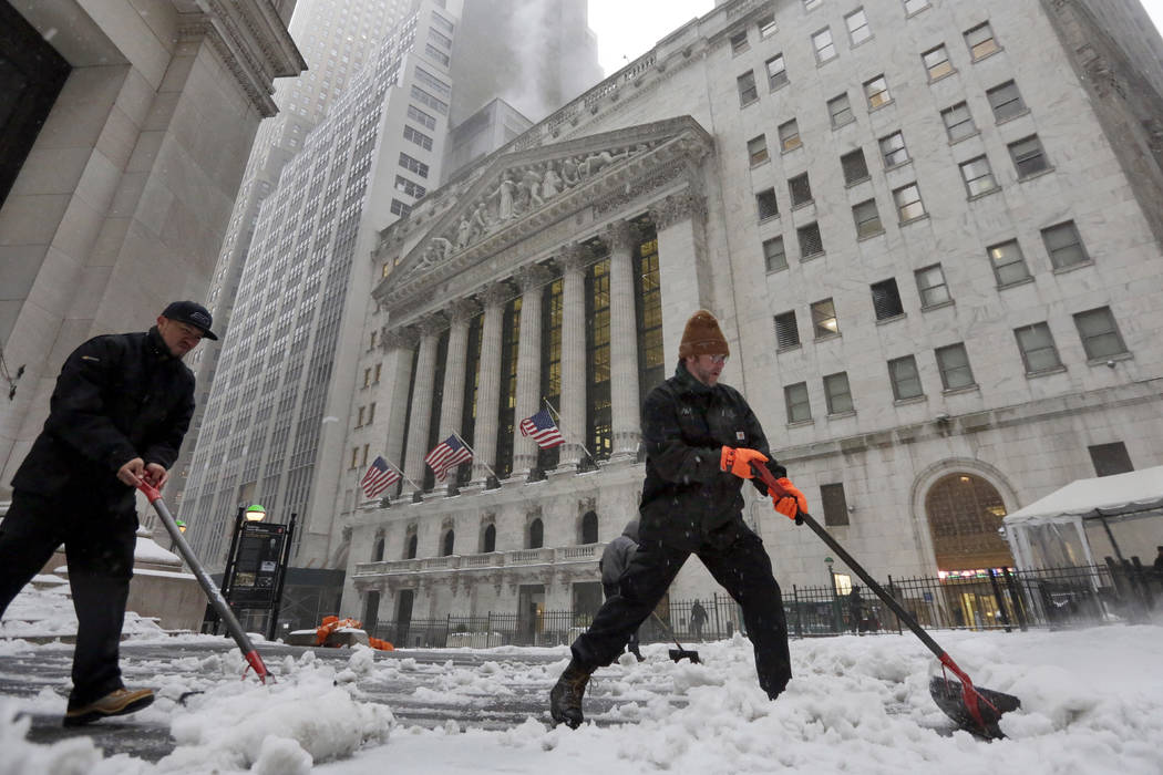 Snow is shoveled from a sidewalk adjacent to the New York Stock Exchange, Tuesday, March 14, 2017.(Richard Drew/AP)
