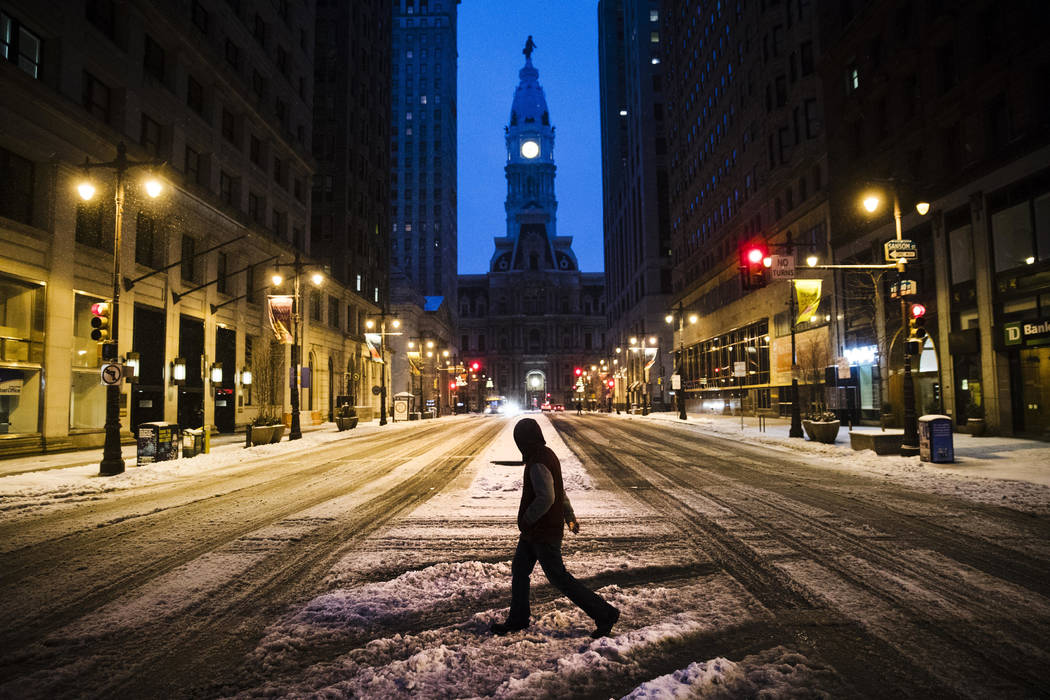 A man crosses South Broad Street in view of City Hall during a winter storm in Philadelphia, Tuesday, March 14, 2017. (Matt Rourke/AP)