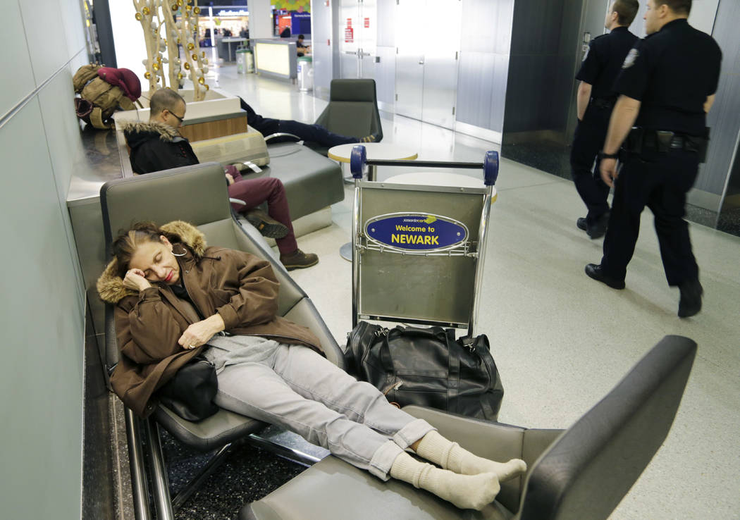 Yvonne Mouskourie, of Tom's River, N.J., makes herself comfortable after her morning flight to Florida was canceled at Newark Liberty International Airport in Newark, N.J., Tuesday, March 14, 2017 ...