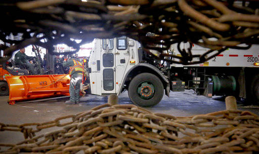Sanitation department personnel prepare a sanitation truck with a plow and follow with wheel chains for snow removal Monday March 13, 2017, in New York. The National Weather Service issued a blizz ...