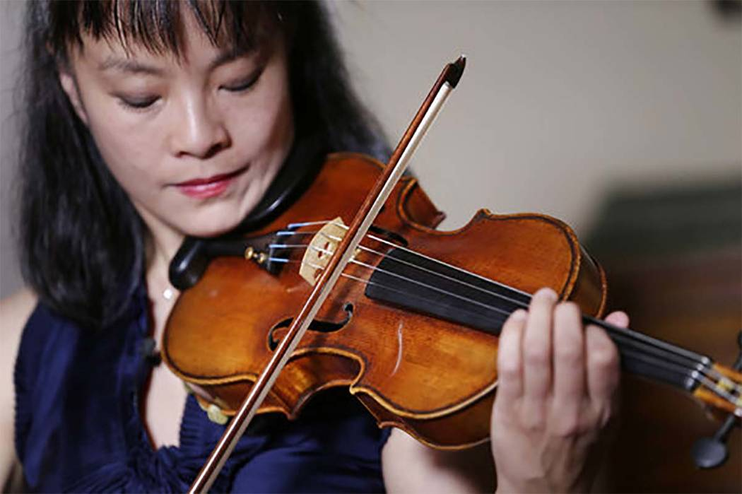 In this Wednesday, March 8, 2017 photo, violinist Mira Wang plays the Ames Stradivarius violin in New York. After a meticulous restoration that took more than a year, the Stradivarius violin that  ...