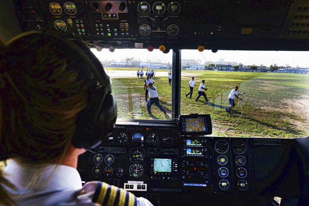 """This Sept. 23, 2015, photo shows ground crew moring the Goodyear Blimp """"Sprit of Innovation"""" as pilot Taylor Laverty brings the ship for a landing at Goodyear Airship Base in Carson, Calif. (Richa ..."""