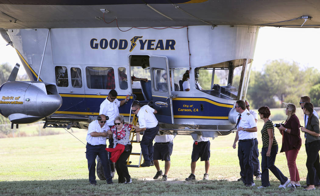 """This Sept. 23, 2015, photo shows ground crew help passengers off of the Goodyear Blimp """"Sprit of Innovation"""" after coming in for a landing at Goodyear Airship Base in Carson, Calif. (Richard Vogel/AP)"""