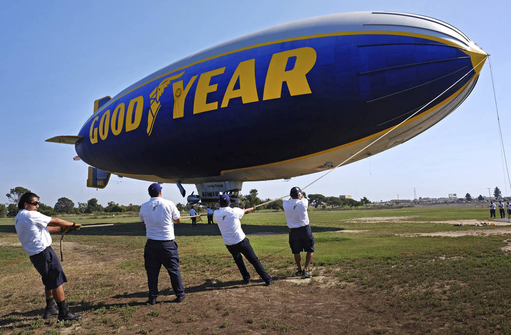 """This Sept. 23, 2015, photo shows ground crew moring the Goodyear Blimp """"Sprit of Innovation"""" as it comes in for a landing at Goodyear Airship Base in Carson, Calif. Goodyear is letting the helium  ..."""