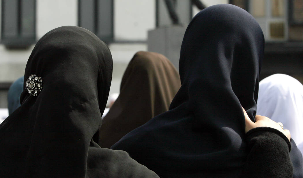 FILE-- In this June 28, 2009 file photo, women gather during a demonstration in Antwerp, Belgium. Private businesses can forbid Muslim women in their employ from wearing headscarve ...