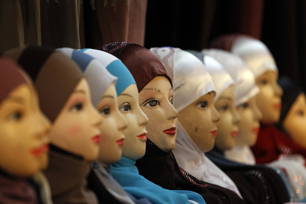 FILE - In this Dec.17, 2011 file photo, mannequins with headscarves are on display at an exhibition hall for the Muslim World Fair in Le Bourget, outside Paris. Private businesses in Europe can fo ...
