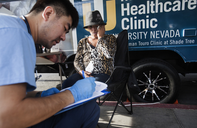 Touro University Nevada physician assistant student Kepeng Lu, left, asks medical questions to patient Traci Triplatt in the homeless corridor on Foremaster Lane on Wednesday, Aug.13, 2014. (Jeff  ...