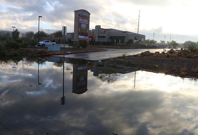 Raising Cane's is reflected in large puddle of rain water on Friday, Dec. 23, 2016, in Henderson. Nevada residents could legally set up barrels to collect rain off their roofs under a bill conside ...