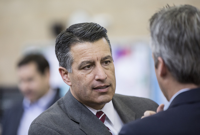 Nevada Gov. Brain Sandoval interacts with the media during a press conference to announce that Democracy Prep Public Schools will assume school operations of Andre Agassi Preparatory Academy in th ...