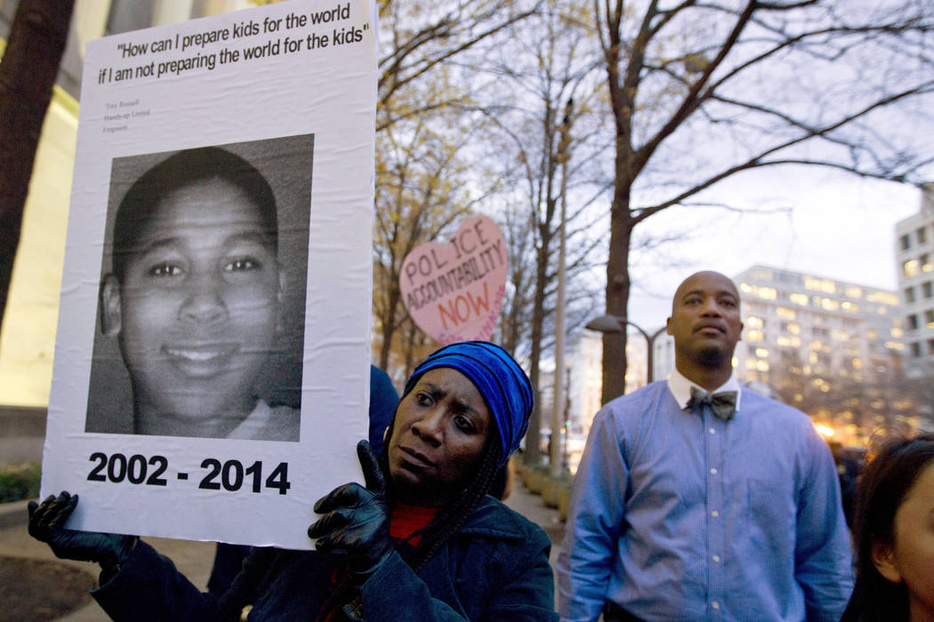Tomiko Shine holds up a picture of Tamir Rice during a protest Monday, Dec. 1, 2014, in Washington, D.C. (Jose Luis Magana/File, AP)