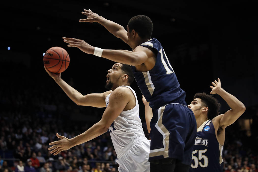 New Orleans' Erik Thomas, left, shoots against Mount St. Mary's Will Miller (11) in the second half of a First Four game of the NCAA college basketball tournament, Tuesday, March 14, 2017, in Dayt ...