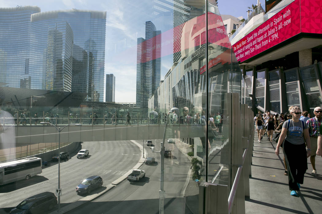 Pedestrians pass on a walkway over Las Vegas Boulevard South near The Cosmopolitan of Las Vegas hotel-casino on the Las Vegas Strip on Friday, March 17, 2017, in Las Vegas. (Bridget Bennett/Las Ve ...