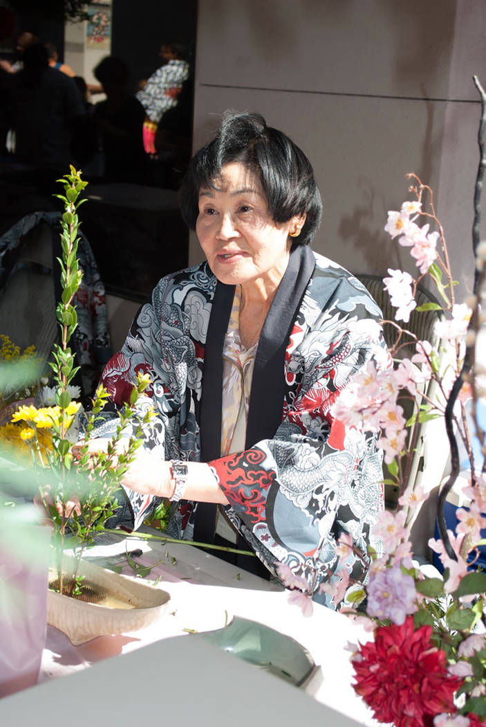 Yukiko Inoue explaining her flower arrangement. The Happi coat she is wearing is created by another member. (Rebecca Snetselaar-special to View)