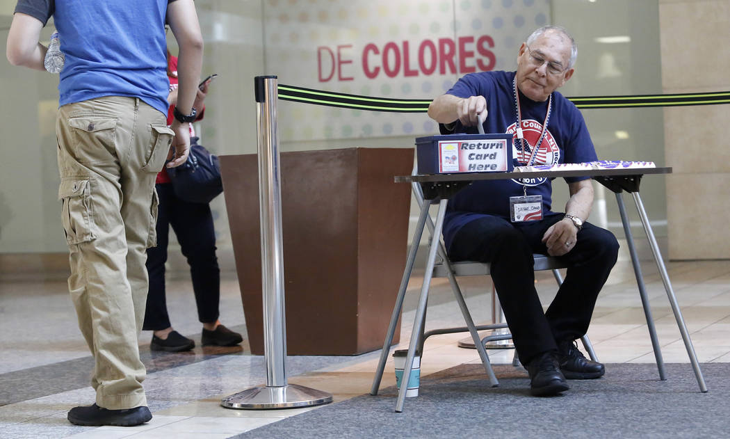 Jesse Cano, 74, places a ballot into a box after a man votes during early election day voting for the Clark County municipal election at the Galleria at Sunset mall on Saturday, March 18, 2017, in ...