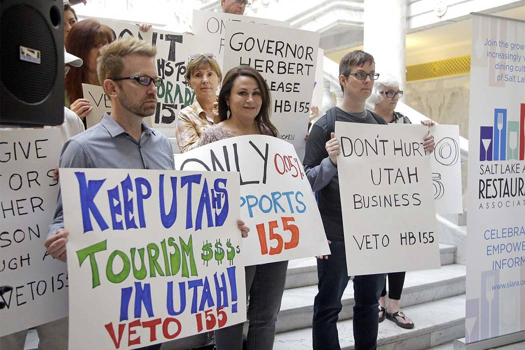 Protesters holds signs during rally at the Utah State Capitol Friday, March 17, 2017, in Salt Lake City. Utah's hospitality industry is urging Gov. Gary Herbert to veto a bill giving Utah the stri ...