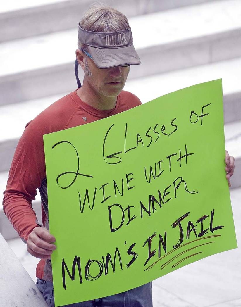 A protester holds a sign during rally at the Utah State Capitol Friday, March 17, 2017, in Salt Lake City. Utah's hospitality industry is urging Gov. Gary Herbert to veto a bill giving Utah the st ...