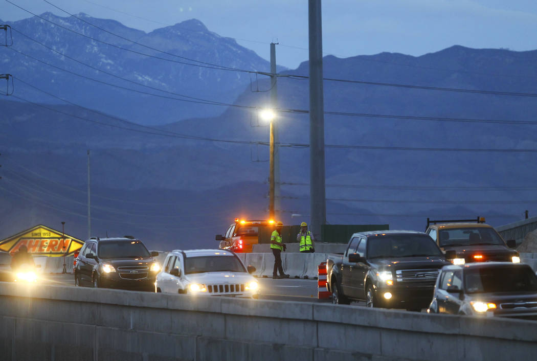 """Nevada Department of Transportation workers look on as eastbound traffic moves along U.S. Highway 95 during the first morning of the """"Big Squeeze"""" at the Spaghetti Bowl in Las Ve ..."""