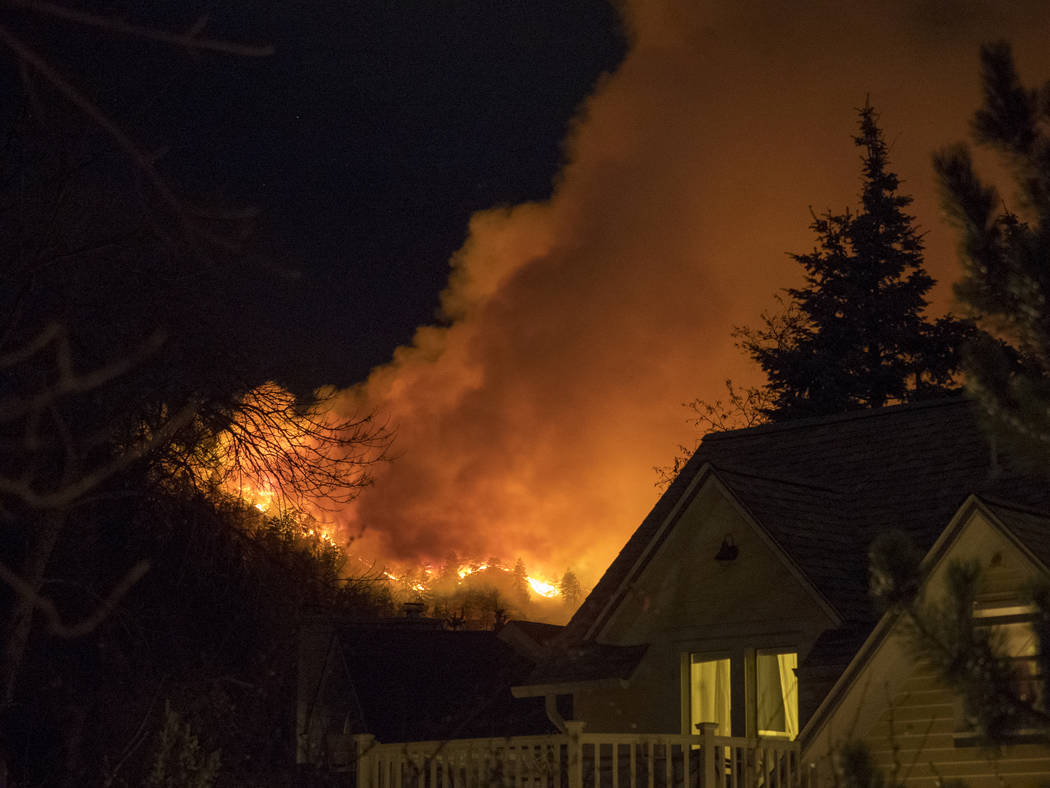 Smoke rises from a wildfire near homes Sunday, March 19, 2017, in Boulder, Colo. Authorities said the small wildfire burning in the mountains forced people from their homes and is filling the sky  ...
