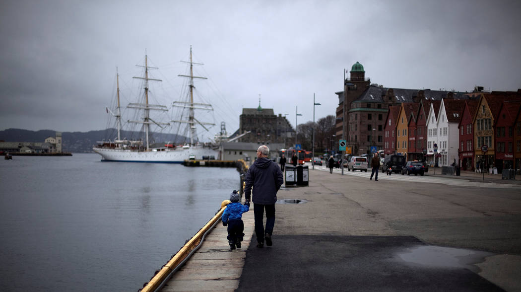 A man walks with a child near the marina in downtown Bergen, southwestern Norway, March 20, 2012. (Stoyan Nenov/Rueters)