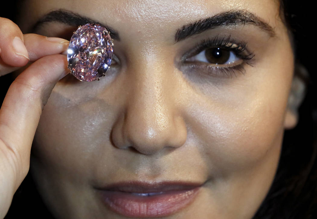 The Pink Star diamond, the most valuable cut diamond ever offered at auction is displayed by a model at Sotheby's auction rooms in London, Monday, March 20, 2017. It is the largest internally flaw ...